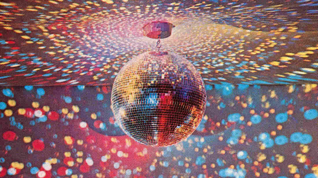 An apparatus that produces a colorful bubble light display covering dark walls and ceiling beneath a large shimmering disco ball, 1960s.