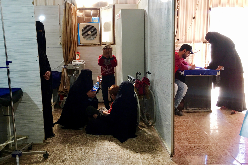 Women sit on the floor as they wait in a clinic at the al-Hol detention camp. (Jane Arraf/NPR)