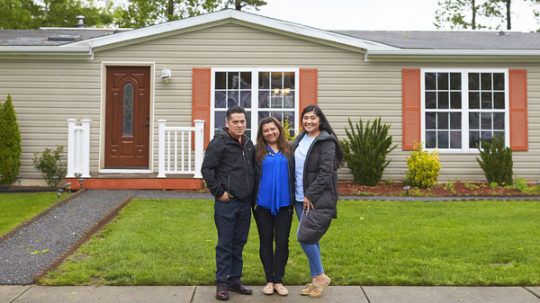 """The Martinez family stands in front of their home in New Jersey. During a speech at her graduation, Alondra said to her parents: """"Mamá, papá, lo logramos."""" Mom, dad, we made it."""