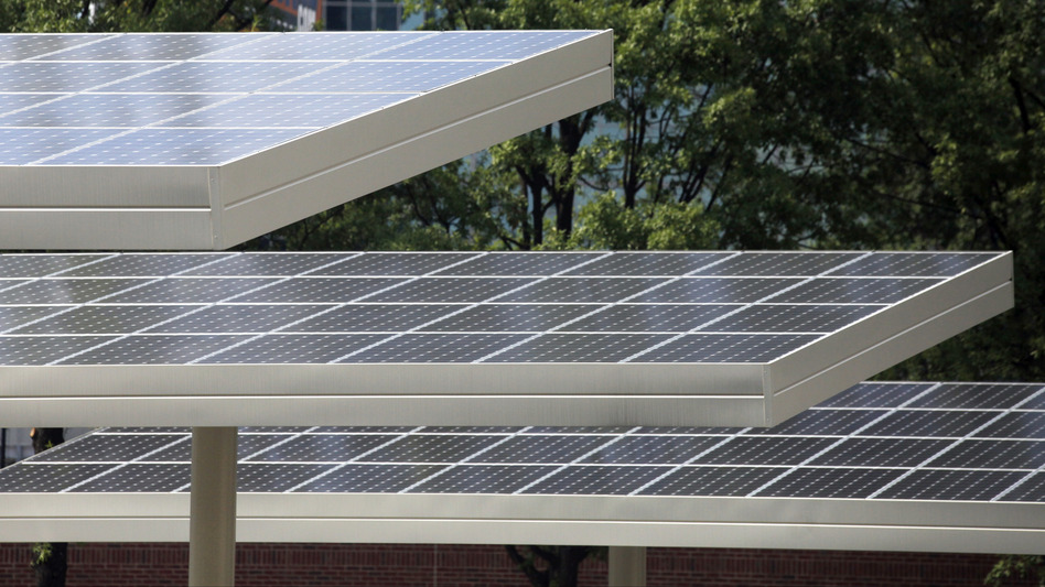 Solar panels cover cars parked in a lot nearby Centennial Olympic Park in Atlanta. The city aims to rely largely on renewable energy by 2035. (Jaime Henry-White/AP)