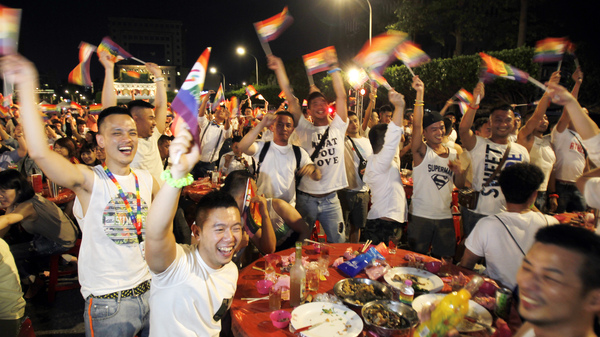 Taiwanese same-sex couples cheer with supporters at a mass wedding banquet in Taipei, Taiwan.