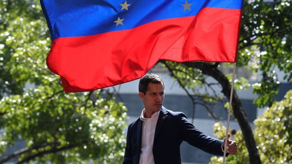 Venezuelan opposition leader Juan Guaidó is pictured under a national flag during a gathering with supporters on April 30, 2019. Delegates for both Guaidó and Nicolás Maduro are slated to hold direct talks in Norway this week aimed at ending the crisis in Venezuela.