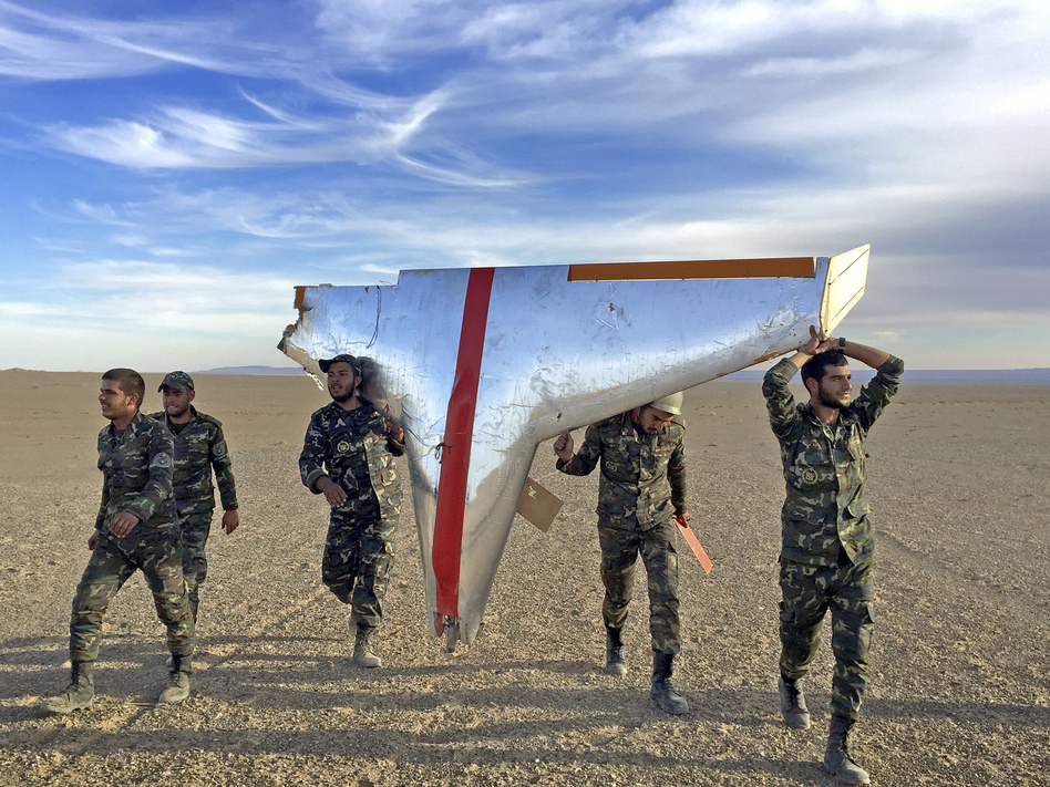 Iranian soldiers carry part of a target drone used in air-defense exercises. Iran is also turning some target drones into low-tech weapons for its proxies. (Iranian Army via AP)