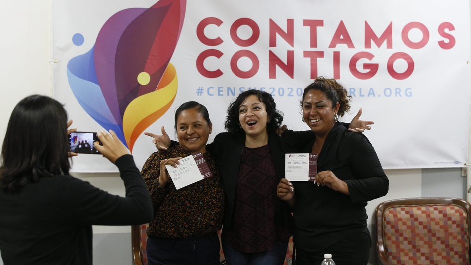 Diana Escamilla (center), an organizer with Coalition for Humane Immigrant Rights in Los Angeles, poses for a photo with volunteers Angeles Rosales and Janet Mendez in front of a 2020 census outreach campaign poster in Spanish. (Damian Dovarganes/AP)