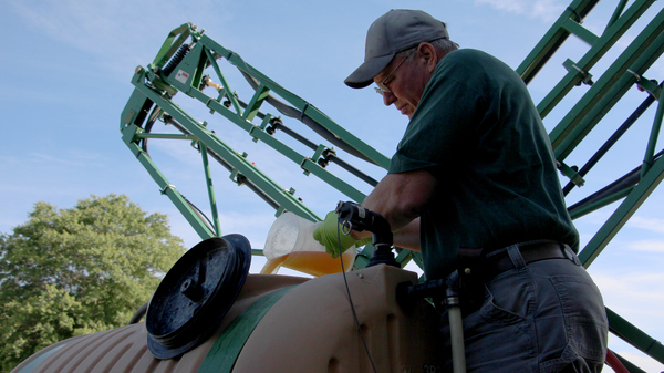 John Draper pours glyphosate into the tank of his sprayer at the University of Maryland