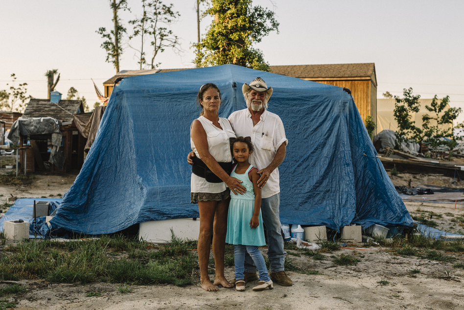 "Shelly and Sam Summers stand with daughter Gabby in front of a makeshift shelter on their rural Bay County property. They opened their backyard to people who were homeless after Hurricane Michael. At the peak, about 50 people lived there. Now, there are 18. ""We still have our home,"" Shelly says. ""They have nothing. So if we can at least offer them the comforts of home, it was worth it."" (William Widmer for NPR)"