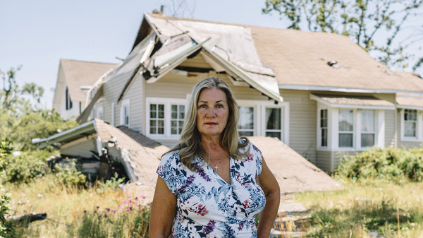 Mayor Margo Anderson stands in front of a storm-damaged home in downtown Lynn Haven, Fla. Much of her town sustained catastrophic damage during Hurricane Michael last year.
