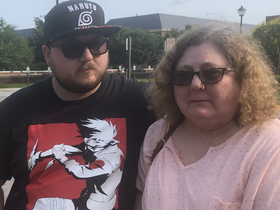 Christi Dewar, a survivor of the Virginia Beach mass shooting, stands with her son, Charles Dewar III, next to the office complex where a gunman killed 12 and injured several others on Friday. (Bobby Allyn/NPR)