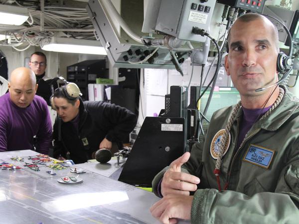 Lt. Cmdr. Alex Diaz oversees traffic on the USS Theodore Roosevelt flight deck.