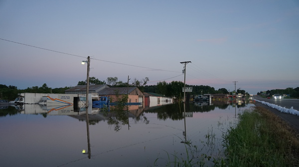 Floodwaters from the Arkansas River line either side of a road in Russellville, Arkansas, engulfing businesses and vehicles.