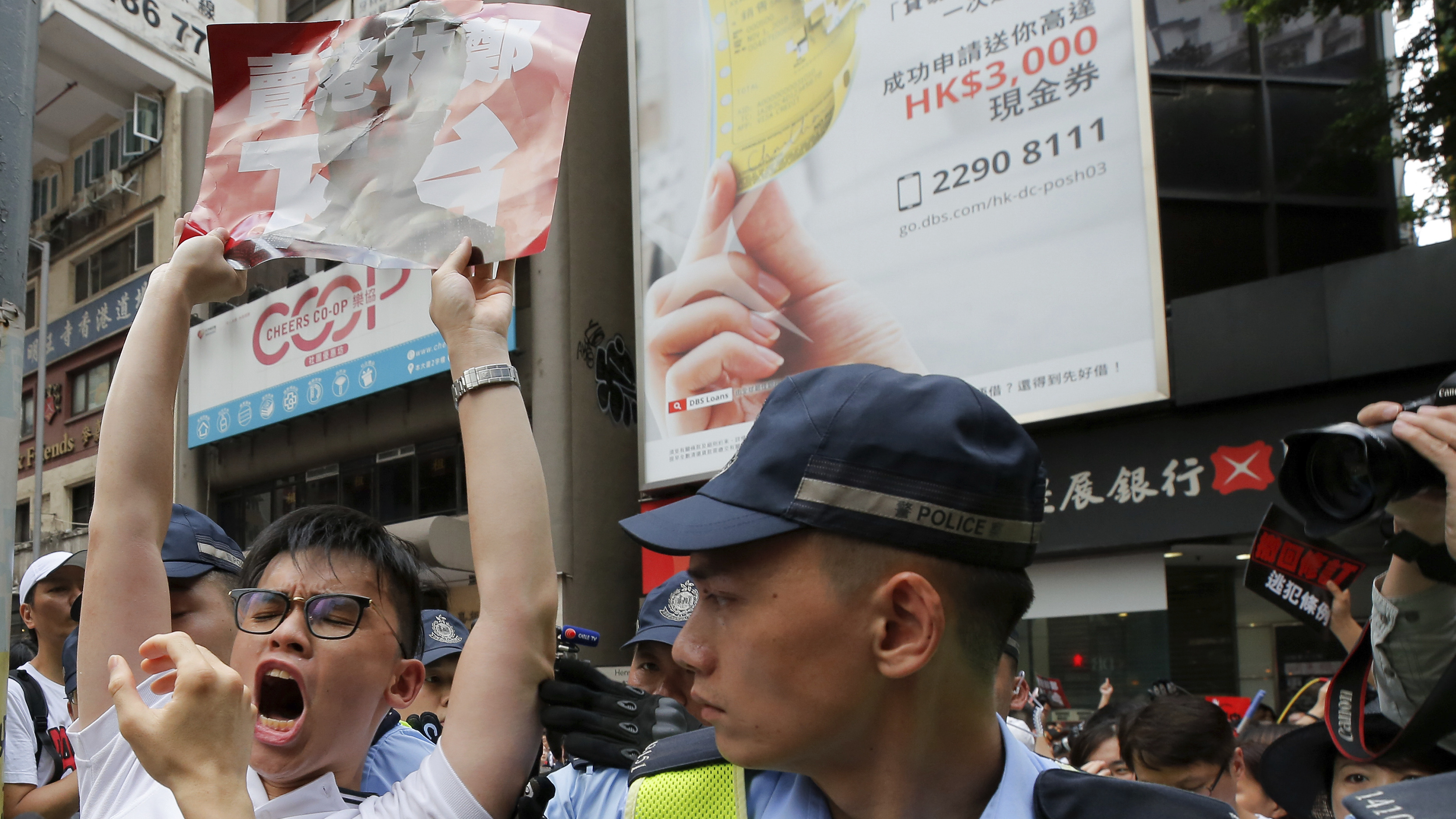 A protester shouts next to policemen during a rally against the proposed amendments to extradition law in Hong Kong.