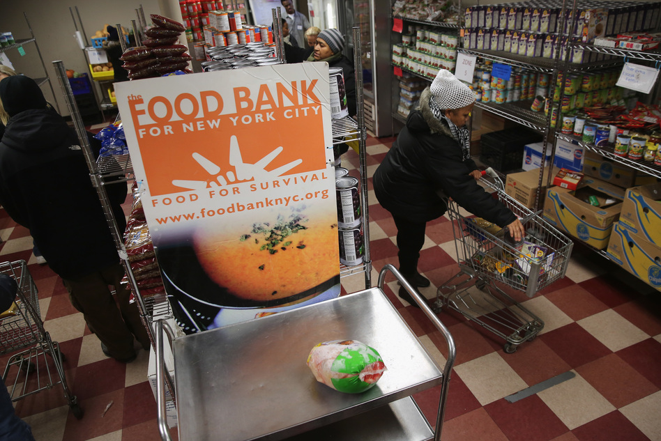 Harlem residents choose free groceries at the Food Bank For New York City in 2013. A number of new rules and actions proposed by the Trump administration could affect poor or low-income people who use government safety net programs. (John Moore/Getty Images)