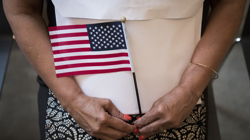A participant in a 2018 naturalization ceremony holds a U.S. flag in New York City. Research by the Census Bureau suggests the citizenship question is highly likely to scare households with noncitizens from taking part in the constitutionally mandated head count. (Drew Angerer/Getty Images)