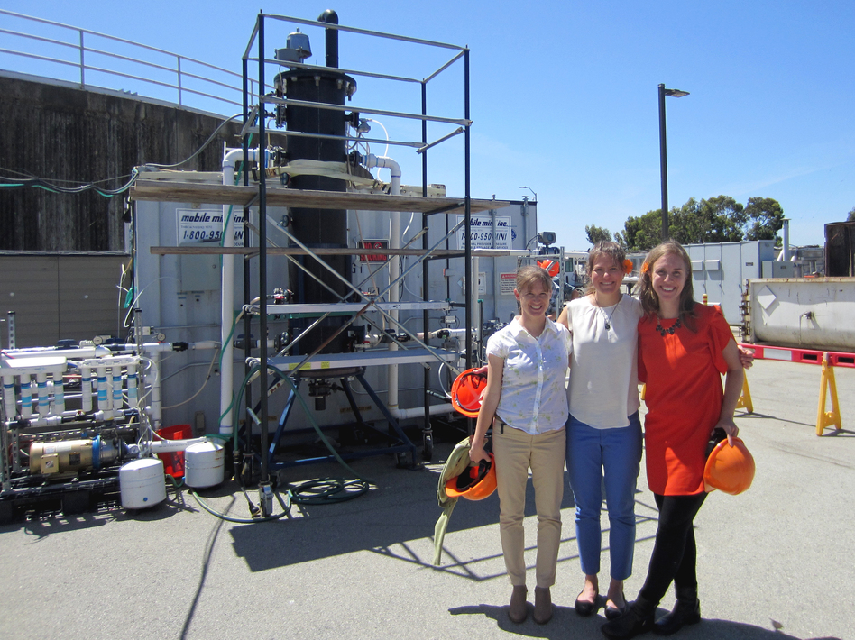 Anne Schauer-Gimenez (from left) Allison Pieja and Molly Morse of Mango Materials stand next to the biopolymer fermenter at a sewage treatment plant next to San Francisco Bay. The fermenter feeds bacteria the methane they need to produce a biological form of plastic. (Chris Joyce/NPR)