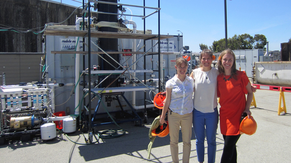 Anne Schauer-Gimenez (left) Allison Pieja (center) and Molly Morse of Mango Materials stand next to the biopolymer fermenter at a sewage treatment plant by the San Francisco Bay. The fermenter feeds bacteria the methane they need to produce a biological form of plastic.
