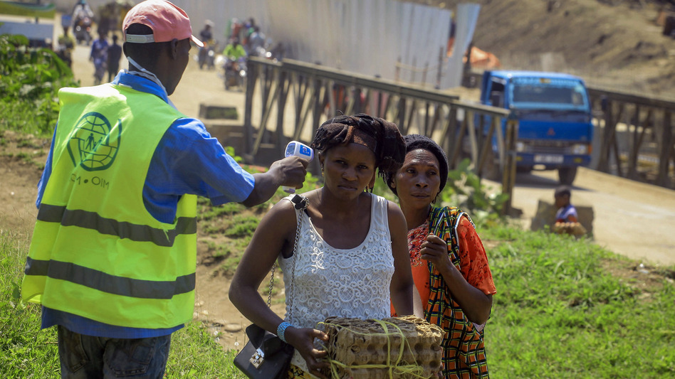 Uganda has reported its first death from Ebola. Here, a health worker takes a woman's temperature at a border crossing between Uganda and Democratic Republic of the Congo, part of an effort to screen for Ebola and prevent its spread. (Al-hadji Kudra Maliro/AP)