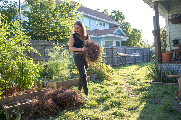 Since her spinal surgery, Liv Cannon has been able to work in the garden and play with her energetic dogs without having to worry about pain. (Julia Robinson for Kaiser Health News)