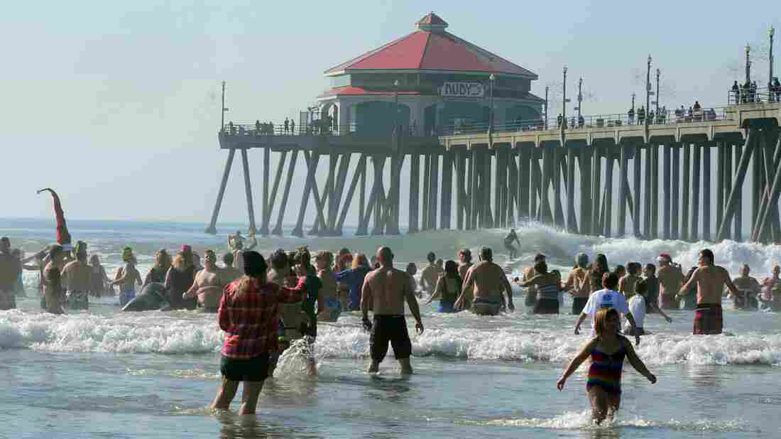 A surfer rides a wave beside Huntington Beach pier as participants at the annual Pier Plaza Plunge spend some time in the chilly waters of the Pacific Ocean at Huntington Beach, California
