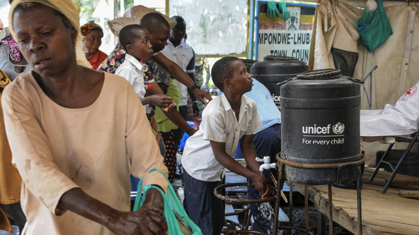 The WHO says the current Ebola outbreak is an emergency in the D.R.C. and nearby region — but not on the international level. Here, people arriving from Congo wash their hands with chlorinated water to prevent the spread of infection at the Mpondwe border crossing with Congo, in western Uganda Friday.