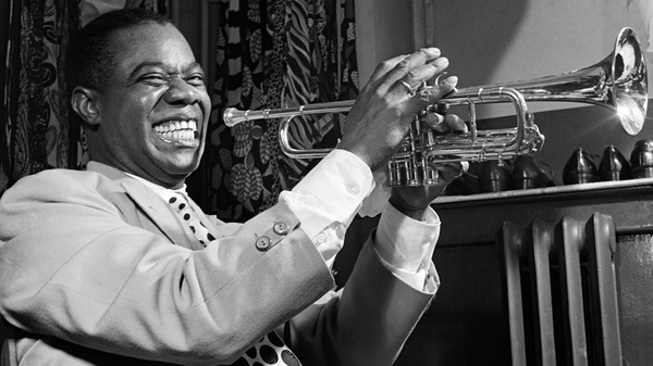 March 1950: Louis Armstrong plays trumpet in his dressing room before a show in New York.