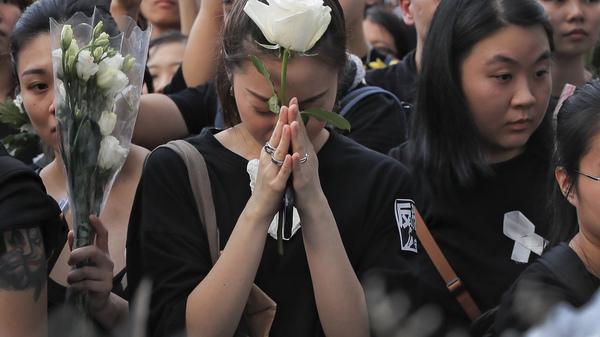 Mourners hold flowers Sunday and pray for a man who fell to his death after hanging a protest banner against an extradition bill in Hong Kong Sunday, June 16, 2019.