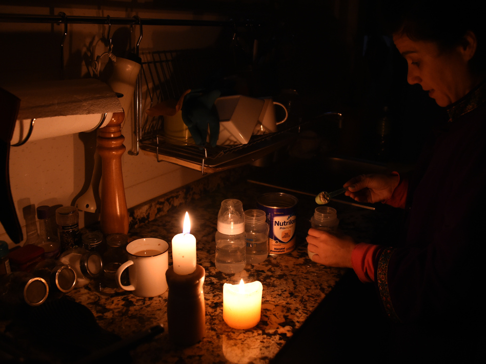 A woman prepares milk bottles Sunday using candles at her home in Montevideo during a power cut. (MIGUEL ROJO/AFP/Getty Images)
