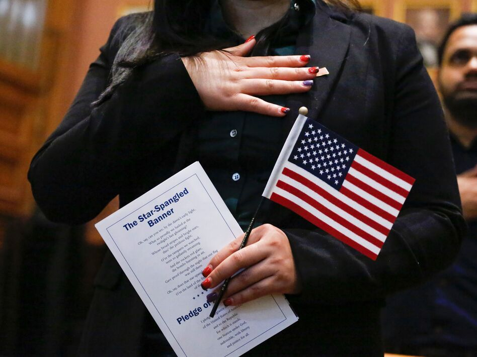 Candidates for U.S. citizenship take the oath of allegiance during a 2017 naturalization ceremony in Jersey City, N.J. A federal judge's order Wednesday could complicate the Census Bureau's plans to finalize census questionnaires and start printing paper forms for the national head count by July 1. (Kena Betancur/AFP/Getty Images)