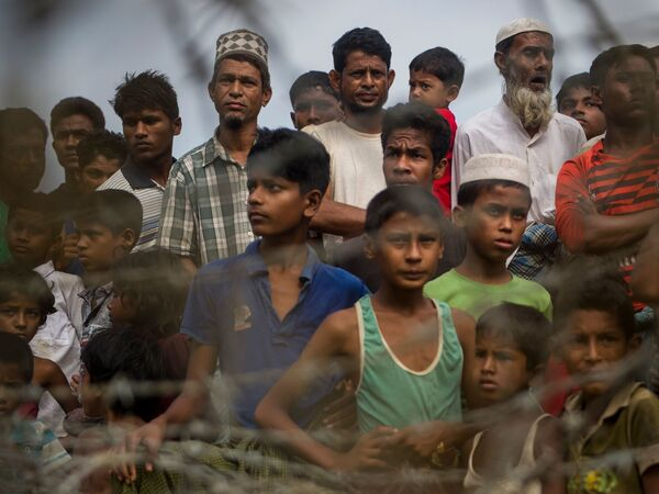 """Rohingya refugees gather in the """"no man's land"""" behind Myanmar's barbed-wire-lined border in Maungdaw district, Rakhine state, in 2018. Some 700,000 refugees fled into Bangladesh following a brutal crackdown by the Myanmar military in 2017."""