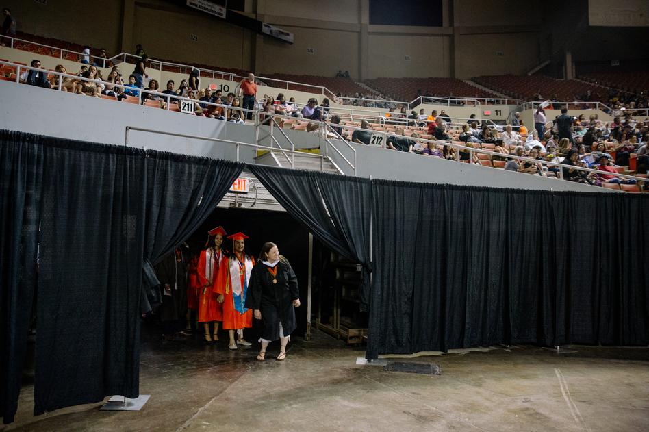 Salutatorian Paulette Olivas, left, stages with fellow Trevor G. Browne High School graduates at the Veterans Colosseum before 2019 Commencement in Phoenix, Ariz. (Caitlin O'Hara for NPR)