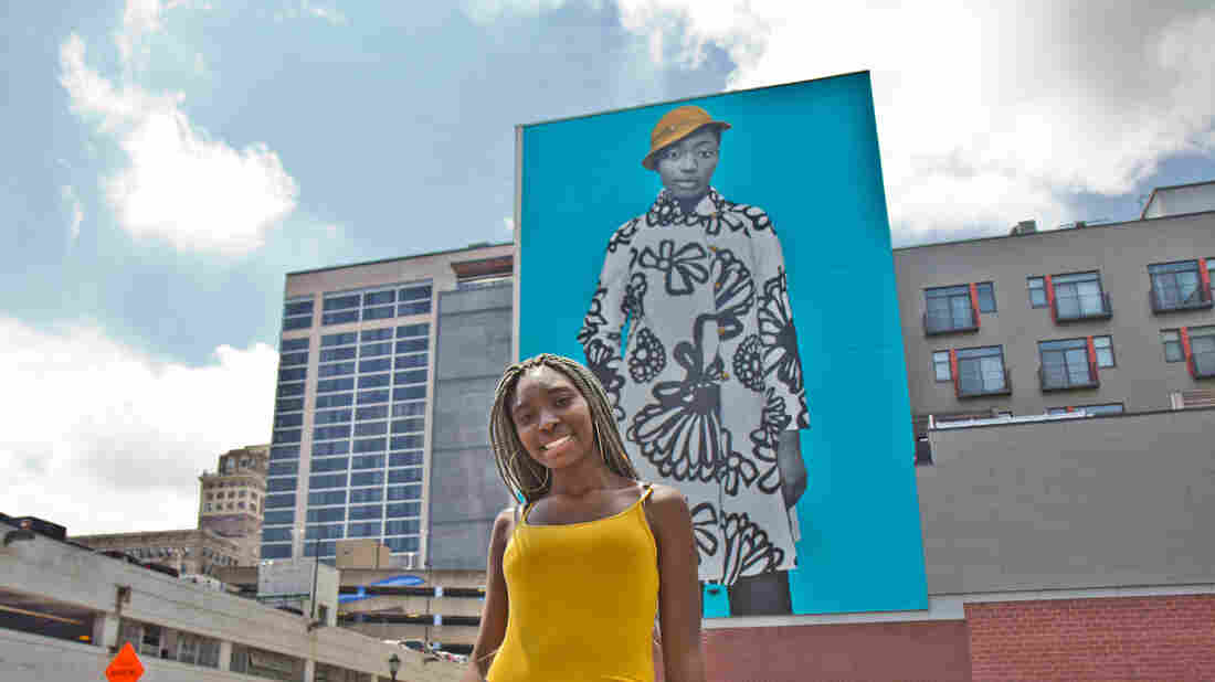 Najee Spencer-Young poses in front of her mural portrait by artist Amy Sherald.