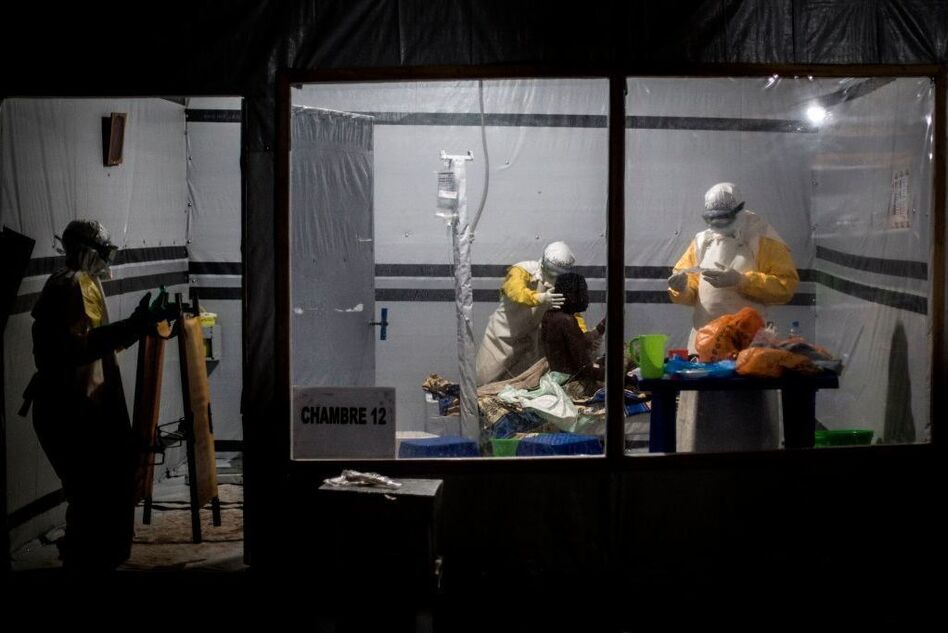 Health workers treat a patient at the Ebola Treatment Center in the city of Butembo, in the Democratic Republic of Congo. It's one of three locations where researchers have been conducting a clinical trial of four experimental treatments for the disease. (John Wessels/AFP/Getty Images)