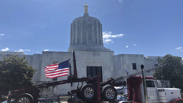 A truck moves around the Oregon state Capitol during a protest against climate bills that truckers say will put them out of business. State Senate Republicans have left the Capitol to avoid a vote on the legislation.