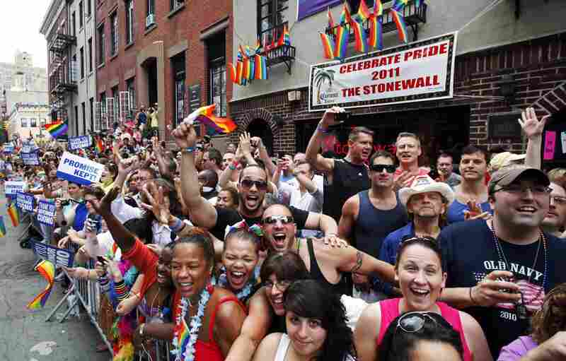People cheer while standing in front of The Stonewall Inn as the annual Gay Pride parade passes, Sunday, June 26, 2011 in New York. One of the world's oldest and largest gay pride parades became a victory celebration after New York's historic decision to legalize same-sex marriage.