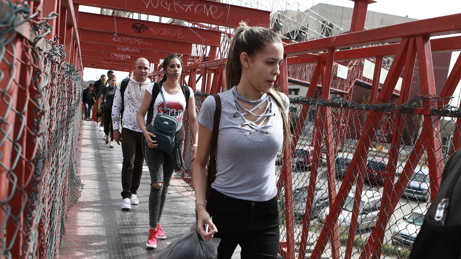 """Cuban migrants cross a bridge in Mexico to be processed as asylum-seekers in the U.S. The labor union representing asylum officers claims the policy formally known as the Migrant Protection Protocols is a """"widespread violation"""" of international and domestic law. (Christian Torres/AP)"""