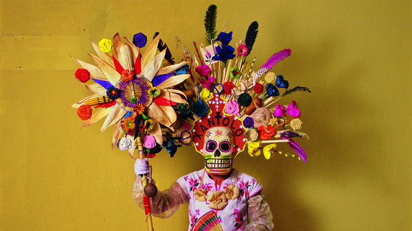 This costume, with corn husks and feathers and paper flowers, is worn by a member of a dance group that gathers in cemeteries and other places to mark Day of the Dead festivities (called Xantolo, the word written above the mask).</body></html>