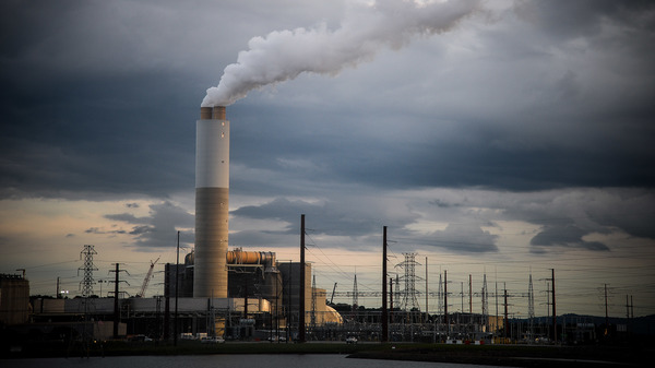 Emissions rise from the Duke Energy coal-fired Asheville Power Plant ahead of Hurricane Florence in Arden, N.C., in September 2018. Regulators are supposed to make sure Duke Energy delivers reliable power at the lowest possible cost — and that
