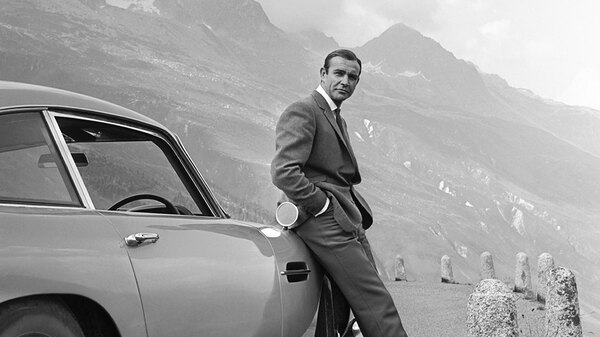 Actor Sean Connery poses as James Bond next to his Aston Martin DB5 in a scene from the United Artists release