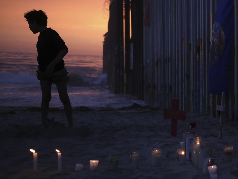 A youth stands Sunday by the border fence that separates Mexico from the U.S., where candles and crosses stand in memory of the father and daughter who died during their journey toward the U.S. (Emilio Espejel/AP)