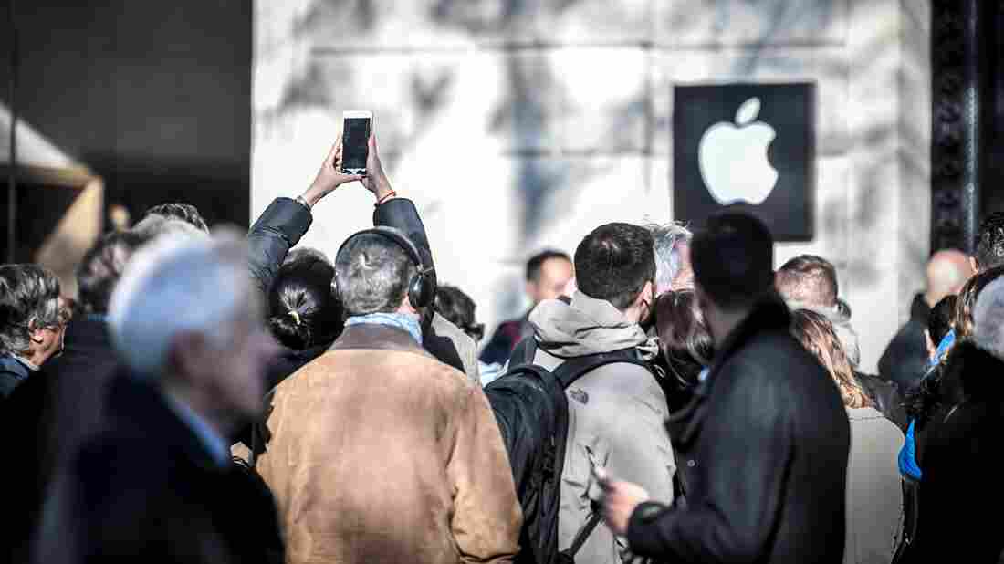 People line up outside the new Apple store on its opening day in Paris in 2017.