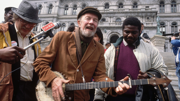 During a civil rights demonstration, folk singer Pete Seeger sings on the steps of the New York State Capital Building.