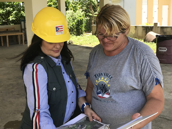 Architect Astrid Díaz (left) talks with Toaville community leader Yarilin Colón about damaged homes in the community.