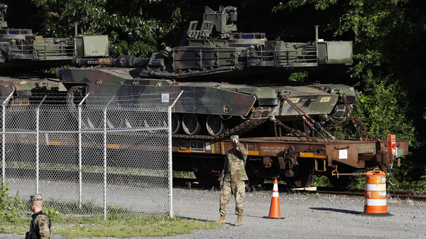 Military police walk near Abrams tanks on a flatcar in a Washington, D.C., rail yard on Monday, ahead of the July 4 celebration that President Trump says will include military hardware.