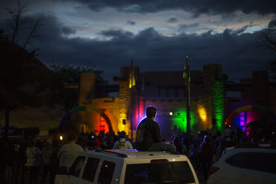 Matthew Slick is silhouetted by the purple light as the Navajo Council Chamber is lit in rainbow colors for Pride on June 28 in Window Rock, Ariz., the capital of the Navajo Nation. (Cayla Nimmo for NPR)