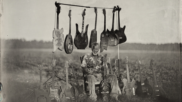 Luthier Freeman Vines sits with his hand-carved guitars in the tobacco field by his house, 2015.