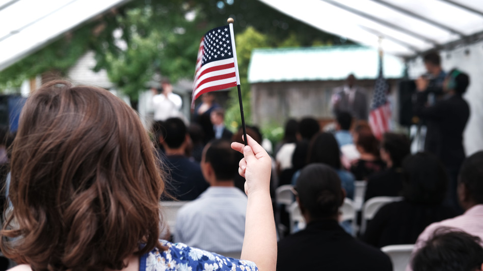 A child holds a U.S. flag at a naturalization ceremony at the Wyckoff House Museum in Brooklyn, on June 14, in New York City. (Spencer Platt/Getty Images)
