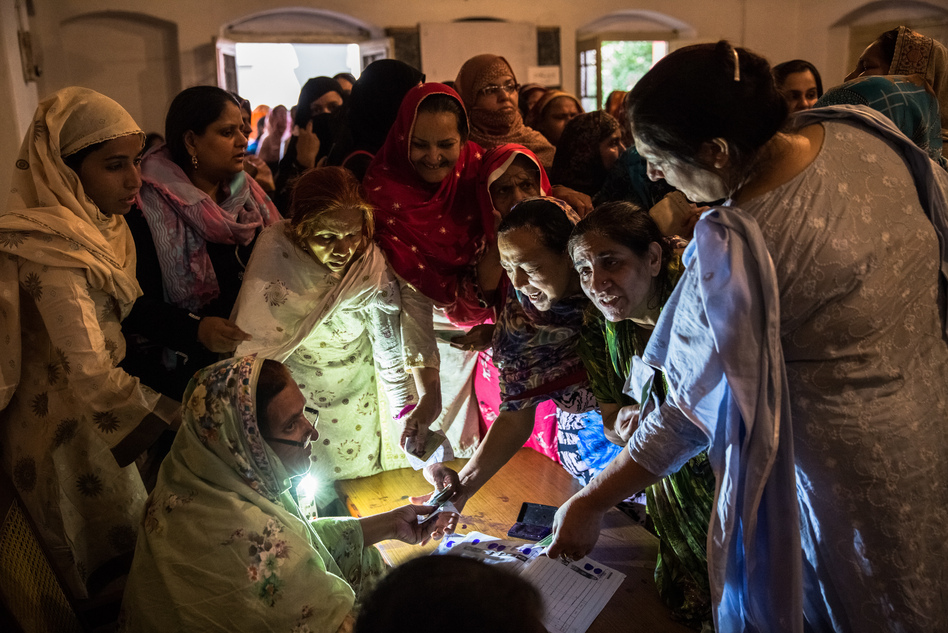 Pakistani women jostle to receive their ballot papers prior to casting their ballot at a polling station on May 11, 2013 in Lahore. A study in <em>The Lancet</em> provides evidence that free and fair elections are associated with a lower burden of chronic diseases. (Daniel Berehulak/Getty Images)