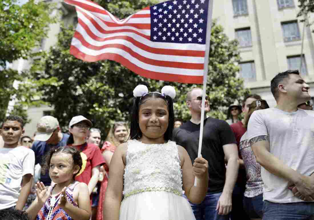 A girl stands waving a flag on the streets of D.C. during the National Independence Day Parade.