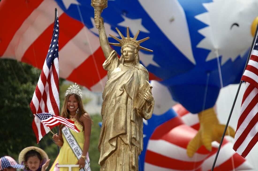"""A golden depiction of the Statue of Liberty and """"Miss VietFest United States"""" are seen during the National Independence Day Parade."""