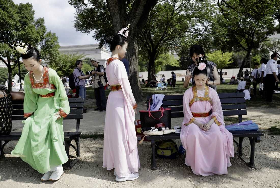 Women in festive clothing get ready during the National Independence Day Parade festivities.