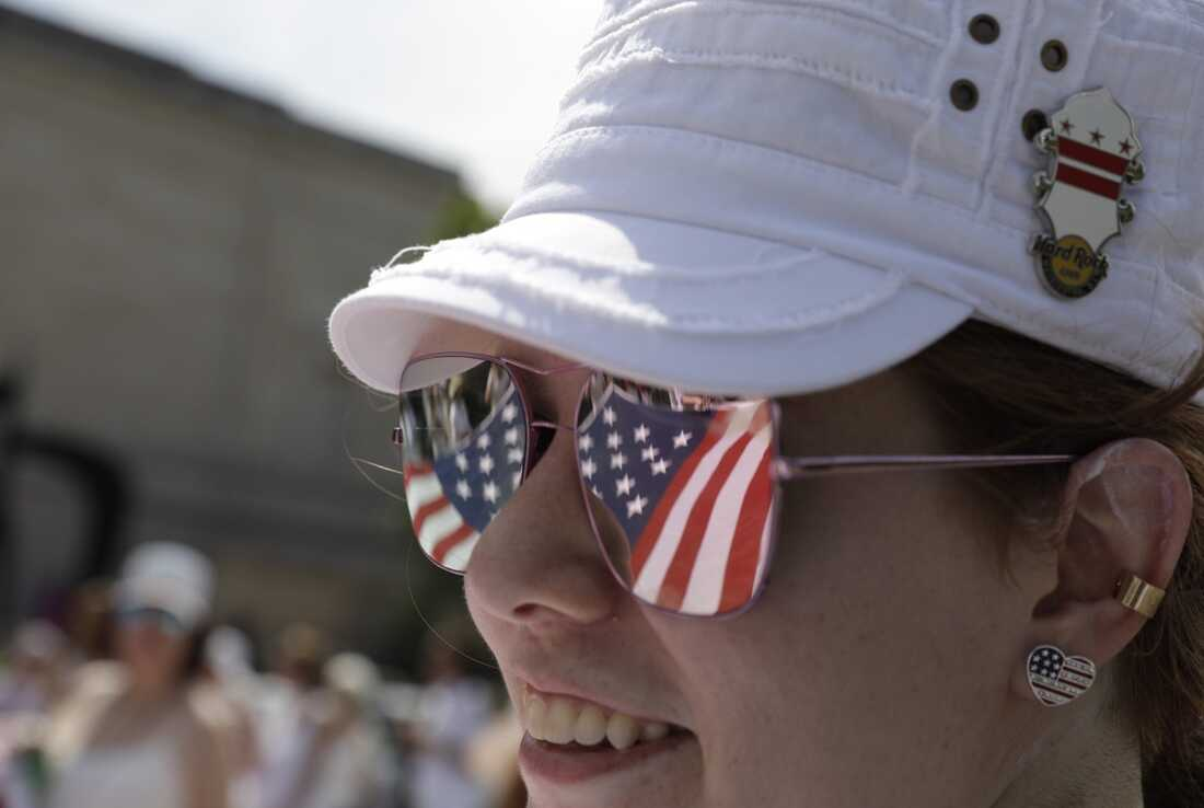 Stars and stripes are reflected in an onlooker's sunglasses during the National Independence Day Parade in Washington, D.C.